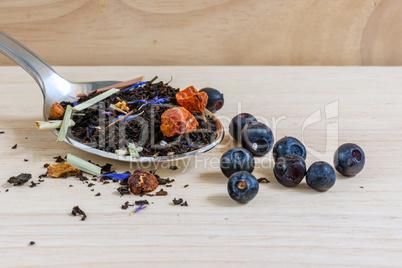 Dry black tea on spoon with blueberries