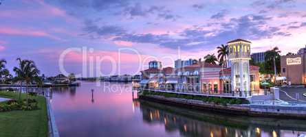 Sunset over the colorful shops of the Village on Venetian Bay
