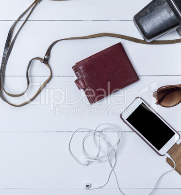leather purse and smartphone with headphones