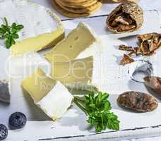 Camembert cheese sliced on a white wooden board