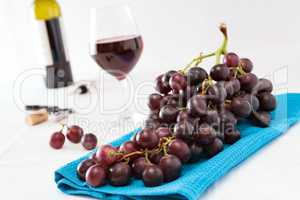 Closeup of a bunch of red grapes and a glass of red wine with a