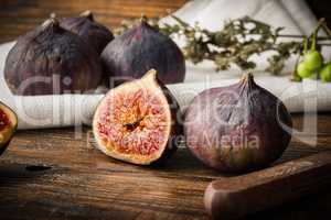 Ripe, purple figs on wooden table with sliced one