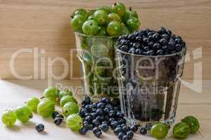 Blueberries and gooseberries in glass with scattered berries.