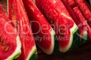 Juicy watermelon slices lying on wooden surface