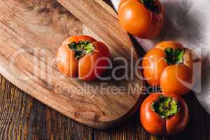 Ripe Persimmons on Cutting Board