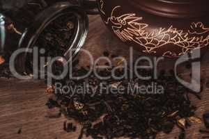 Asian teapot on stand and jar with scattering of tea