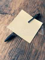Sticky note with a pen on a table