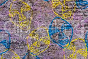 Worn brick wall with graffiti faces background texture.