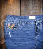 blue jeans with a bouquet of flowers in a front pocket