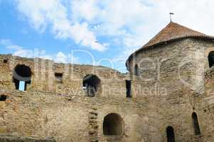 Fortress tower with tiled roof on blue sky background. Location