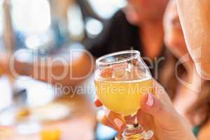 Female Hand Holding Glass of Micro Brew Beer At Bar