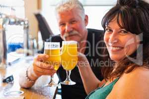 Attractive Middle-Aged Couple Toasting Glasses of Micro Brew Beer