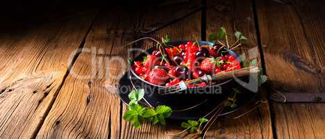 Bowl with different fruits such as strawberry, red currant, and