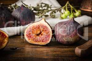 Ripe seasonal figs on wooden table with sliced one
