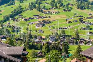 The picturesque Swiss town of Grindelwald. Traditional wooden chalets in summer, in front of the North side of the Eiger mountain, surrounded by bright green pastures