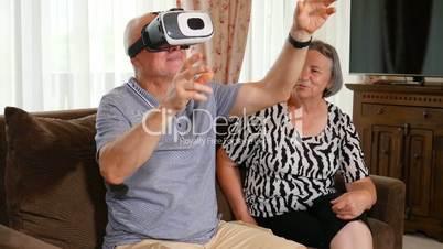 Positive senior couple trying up virtual reality glasses