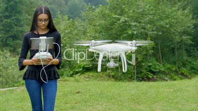Young woman controlling drone with a transmitter remote control