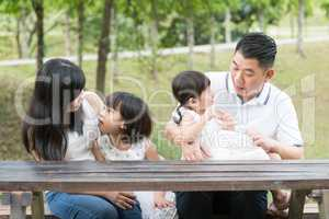 Asian family bonding outdoors with empty table space.