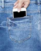 female hand holds a white phone in the back of the blue jeans