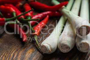 Mexican hot chili peppers with lemongrass scattered on the wooden table