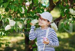 Child smelling white lilac