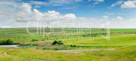 Landscape with hilly field and blue sky. Wide photo.