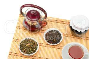 Teapot, cup of tea, jam jar and tea leaves isolated on white bac