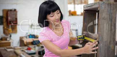 Composite image of woman measuring furniture with tape measure