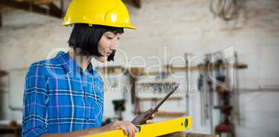 Composite image of female architect measuring plywood with engineer scale