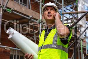 Male Builder Foreman Architect on Building Site Using Phone and