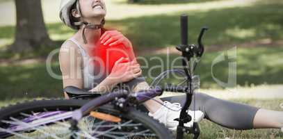 Composite image of female bicyclist with hurt leg sitting in park