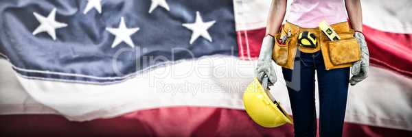 Composite image of woman with tool belt and holding hard hat against grey background