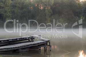 Old ruined pier on the river on a foggy morning.