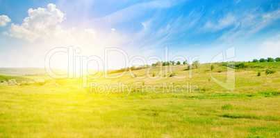 Hilly green fields and sunrise on a blue sky. Wide photo.