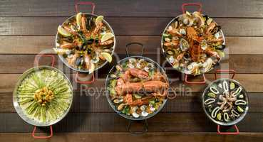 Assorted paella on wooden table, above view