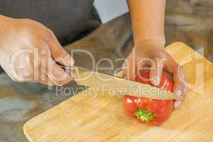 Chef cutting red bell pepper on wooden broad