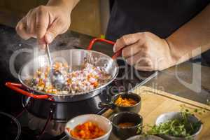 Chef is frying food ingredient for cooking paella