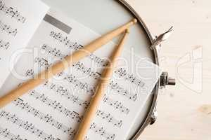 Music score drumsticks and drum tuner over a snare drum