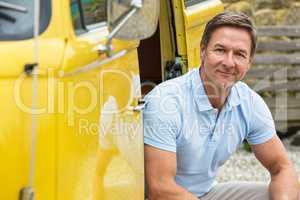 Happy Middle Aged Man Drinking Sitting In Doorway of Van or Bus