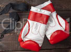 pair of red leather boxing gloves and elastic black bandage