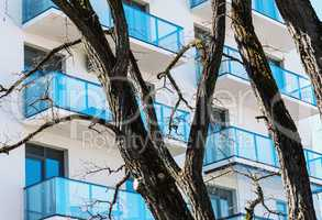 Residential building balconies with trees in foreground
