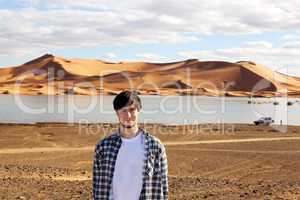Young man in the desert at the lake with sand dunes in Morocco