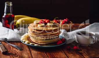 Pancakes with Fruits, Maple Syrup and Cup of Tea.