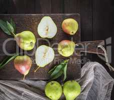 fresh ripe green pears lie on a brown wooden board