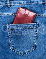 brown leather purse lies in the back pocket