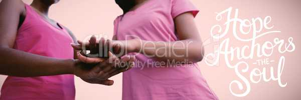 Composite image of two black women joining hands