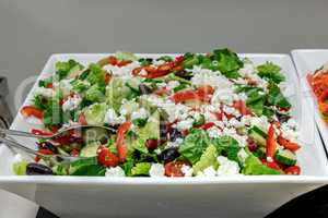 Greek salad including olives, feta cheese, lettuce, cucumbers, a