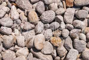Gray pebbles on the coast pile of sea stones and stones on the beach