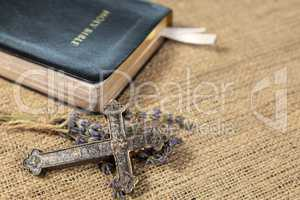 Christian cross on lavanda flowers next to Holy Bible