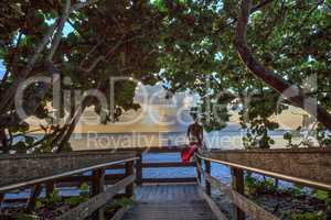 Young woman sits on a fence overlooking the ocean and beach in B